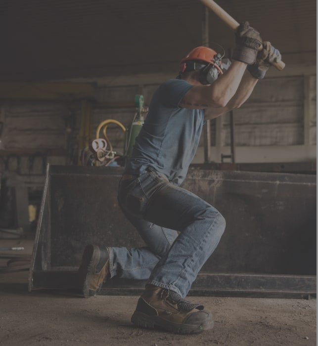 A worker swinging a sledge hammer.