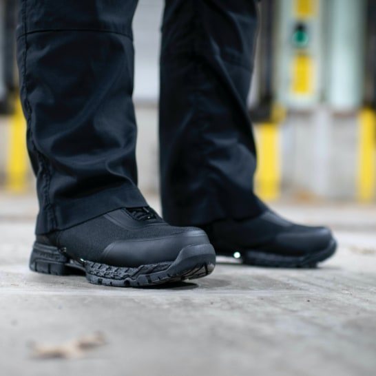 A person wearing black Hytest boots.